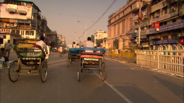 bicycles and rickshaws move along a street in delhi, india. - rikscha stock-videos und b-roll-filmmaterial