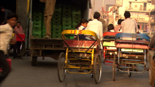 bicycles and rickshaws move through a street in delhi, india. - rikscha stock-videos und b-roll-filmmaterial