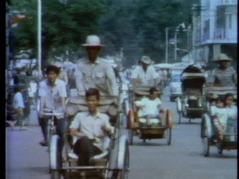 bicycles and rickshaws ride among the few automobiles in phnom penh, cambodia. - rickshaw stock videos & royalty-free footage