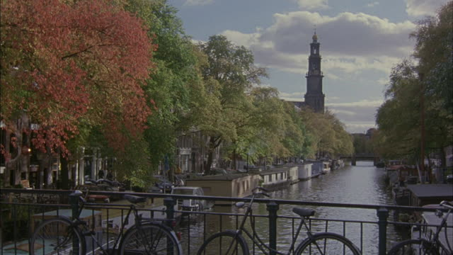 bicycles cross a bridge over a canal in amsterdam. - lockdown stock-videos und b-roll-filmmaterial