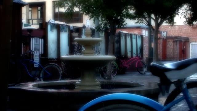 vídeos de stock, filmes e b-roll de bicicletas bloqueada por uma fonte de água foco suave - antiquário loja
