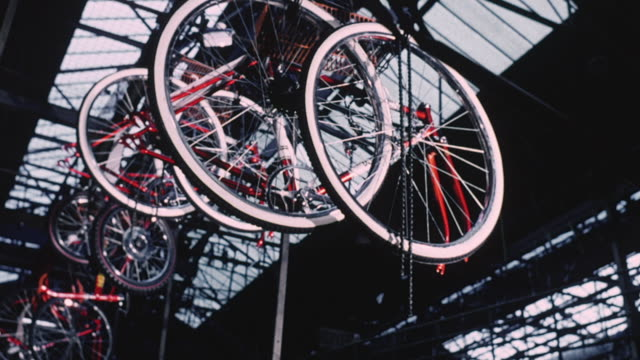 1974 montage bicycles moving on assembly line and workers assembling bicycle parts in a factory / united kingdom - 1974 bildbanksvideor och videomaterial från bakom kulisserna