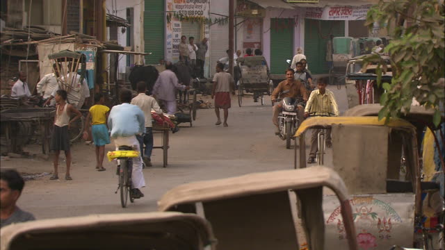 vídeos de stock, filmes e b-roll de bicycles, pedicabs and motorcycles pass through a small town in india. - jinriquixá puxado por bicicleta