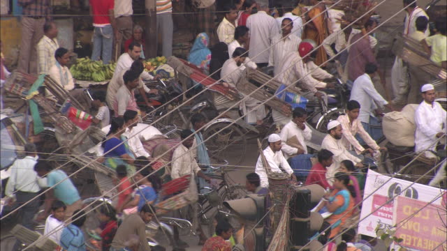 bicycles, pedicabs and pedestrians surge along a congested street in india. - ペディキャブ点の映像素材/bロール