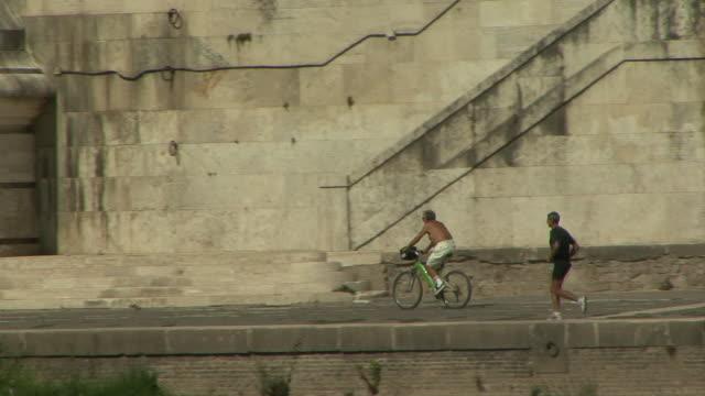 ws pan zo bicyclist and runner on banks of tiber under vittorio emanuele ii bridge / rome, italy - テベレ川点の映像素材/bロール