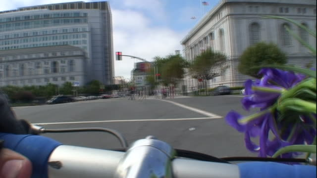 vídeos de stock e filmes b-roll de a bicyclist carries a bouquet of flowers on the handlebars as he pedals through san francisco. - san francisco