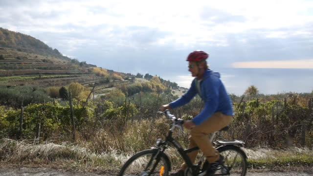 vidéos et rushes de bicyclist pauses at edge of mountain road, looks off to sea - casque de vélo