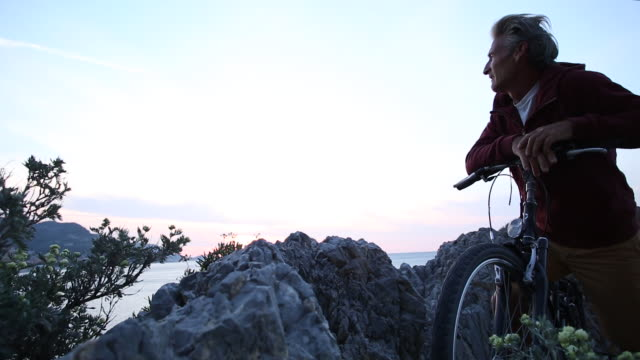Bicyclist pauses on shoreline rocks, looks out to sea at sunrise