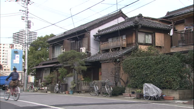 A bicyclist pedals past old houses in Old Town Tokyo.
