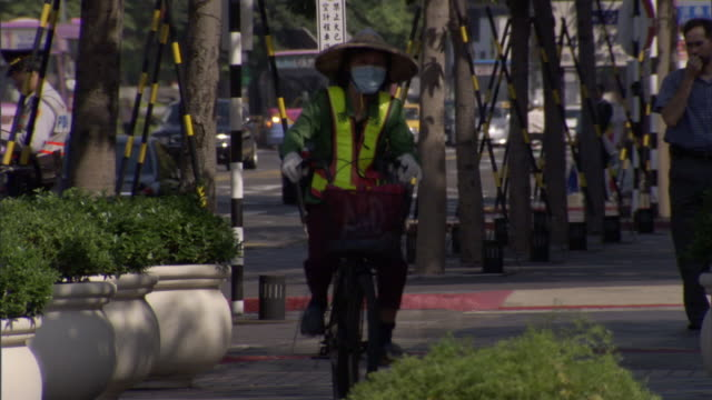 a bicyclist wearing a hat and a mask rides along a sidewalk. - taipei stock videos & royalty-free footage