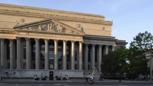 bicyclists and pedestrians move past the entrance to the national archives building early in the day. - national archives washington dc stock videos and b-roll footage