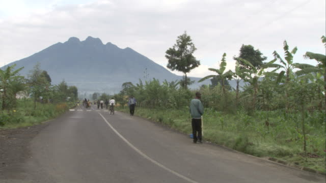 bicyclists and pedestrians travel along a road toward a volcano in volcanoes national park, rwanda. available in hd - ルワンダ点の映像素材/bロール