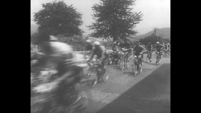 bicyclists following car for tour de france / ws snowcovered mountains / ws cyclists going uphill in the mountains / winner louison bobet crossed... - ツール・ド・フランス点の映像素材/bロール