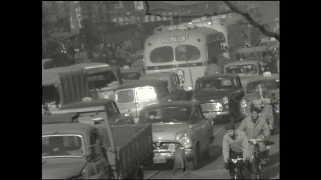 bicyclists pass traffic on a congested street; a streetcar slows in a traffic jam. - showa period stock videos & royalty-free footage