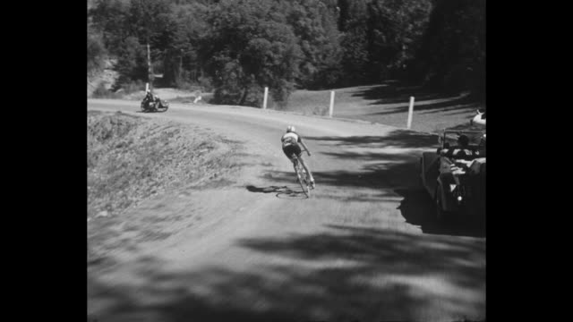 bicyclists pedaling uphill through mountains / cu cyclist / lone cyclist leading / crowd waving / cyclist crosses finish line in lap / cu priest in... - 1951 bildbanksvideor och videomaterial från bakom kulisserna