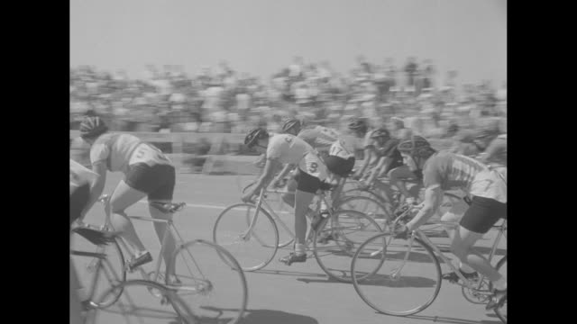 Bicyclists racing at Fresh Meadows in Flushing / cameraman Lou Hutt working a movie camera atop car surrounded by female race contestants / MS pan of...