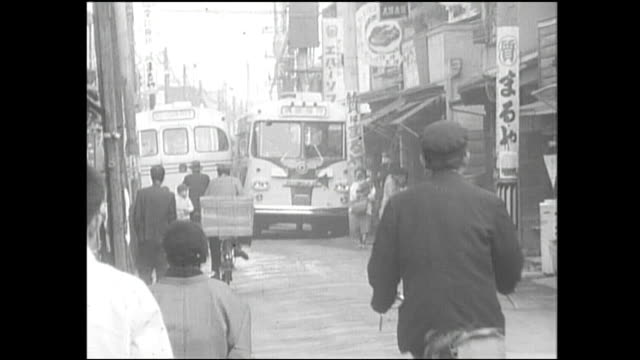 bicyclists ride down a narrow street as buses pass close by. - showa period stock videos & royalty-free footage