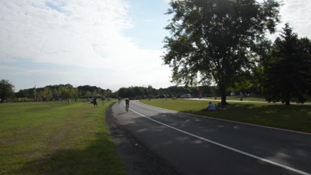 vídeos de stock e filmes b-roll de bicyclists ride down a small road at the new jersey state triathlon in mercer county park. - triatleta