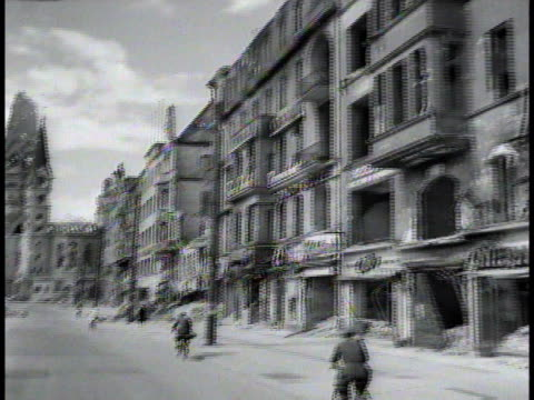 bicyclists ride past demolished buildings as workers begin cleaning up the mess / berlin germany - 1945 stock videos & royalty-free footage
