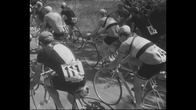 bicyclists ride through crowdfilled paris streets at the start of the tour de france / cu cyclists / cyclists cross train tracks and pass a windmill... - ツール・ド・フランス点の映像素材/bロール