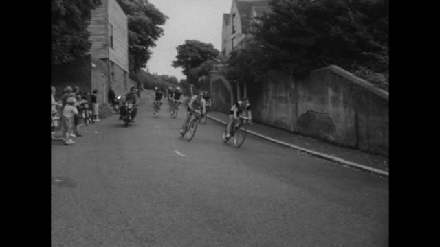 bicyclists riding by in street / vs cyclist riding looking at camera / cyclists riding through street of village with bystanders cheering them on /... - tour of britain stock-videos und b-roll-filmmaterial