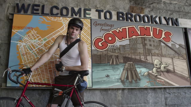 bicyler posing in front of gowanus poster in brooklyn - poster stock videos & royalty-free footage