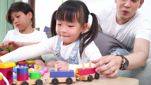 big asian brother, little brother, little sister spending weekend activities together, playing wooden toys in the living room of a home. concept of city life, learning, sibling with simple living. - 12 13 years stock videos & royalty-free footage
