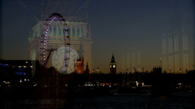 year anniversary; ext / night westminster: big ben clock and tower london eye, houses of parliament and big ben seen from across thames low angle... - ランベス点の映像素材/bロール