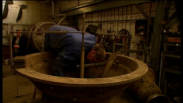 150 year anniversary whitechapel ext sign on wall 'whitechapel bell foundry' worker leaning inside large bell mould whilst cleaning it bell makers at... - foundry worker stock videos and b-roll footage