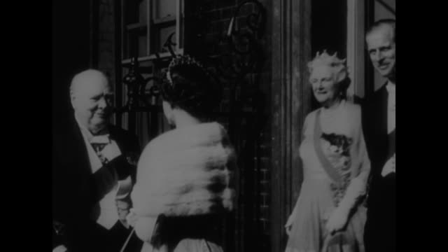 Queen Elizabeth exits 10 Downing Street outgoing prime minister Winston Churchill bows Lady Clementine Churchill follows with Prince Philip the...