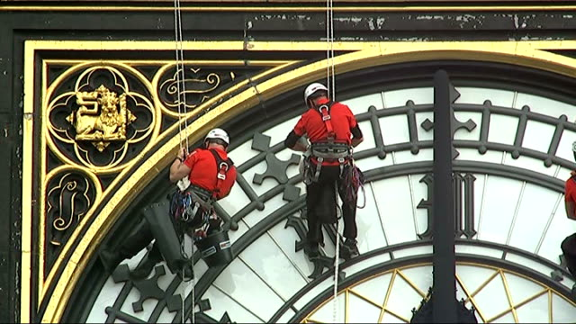 big ben clock face cleaned by abseilers team of people abseiling down the clock face of big ben to clean the 312 panes of pot opal glass - tower stock videos & royalty-free footage