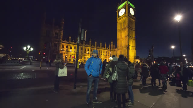 Big Ben clock tower and tourists at night on Westminster Bridge in London.