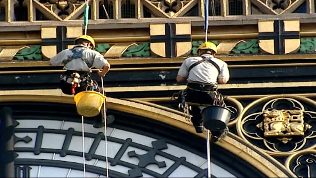 big ben clock tower stopped for repairs ext minute hands of big ben clock face turns to 12 o' clock position workers absail down to face of clock to... - face down stock videos & royalty-free footage