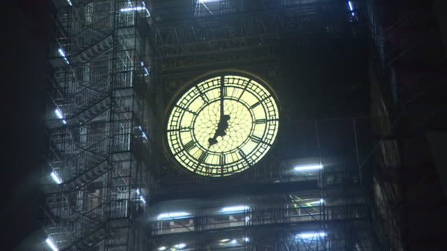 big ben illuminated at night and surrounded by scaffolding showing the time of seven o'clock - instrument of time stock videos & royalty-free footage