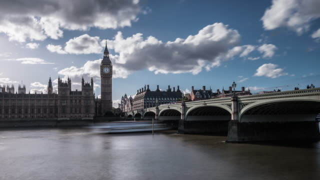 big ben the houses of parliament and westminster bridge are silhouetted against the blue sky and rapidly moving clouds in late afternoon sunlight - westminster bridge stock videos and b-roll footage