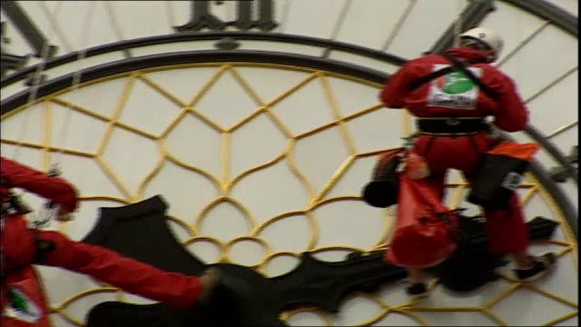 stockvideo's en b-roll-footage met big ben to go silent as maintenance work begins tx abseilers cleaning big ben clockface - klokkentoren met wijzerplaat