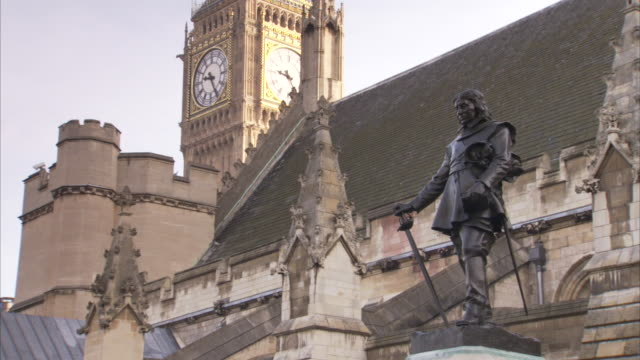 big ben towers over the spires of parliament and the statue of oliver cromwell. - britisches parlament stock-videos und b-roll-filmmaterial