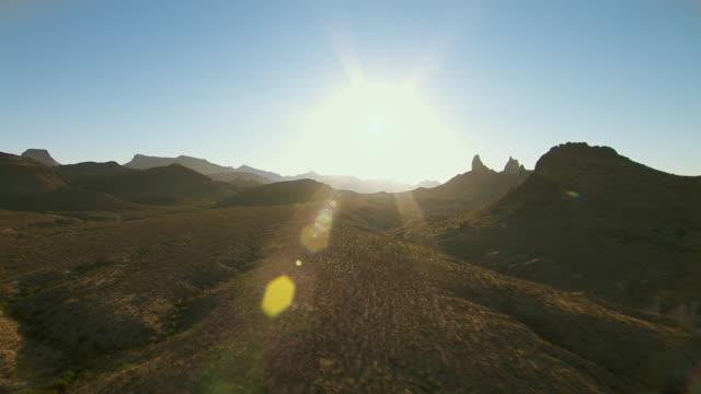 Big Bend landscape with Mule Ear Peaks, backlit at golden hour.