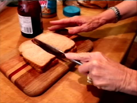 stockvideo's en b-roll-footage met s on a cutting board in the kitchen big brands like jif skippy and peter pan are raising their prices due to a hot and dry summer that devastated the... - kraft