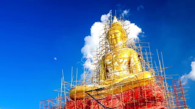 vidéos et rushes de grande statue de bouddha en cours de restauration avec les gens, timelapse - lieu de culte