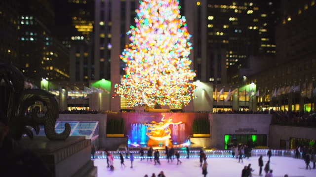 vidéos et rushes de big christmas tree stands among the midtown manhattan buildings in rockefeller center at the night in new york city ny usa on jan. 02 2020. - sapin de noël