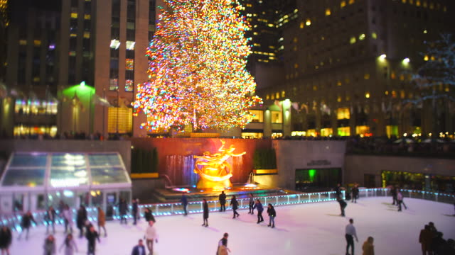 big christmas tree stands among the midtown manhattan buildings in rockefeller center at the night in new york city ny usa on jan. 02 2020. - rockefeller center christmas tree stock videos & royalty-free footage