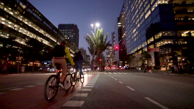 Big city crossing at dusk with movement of cars and bicycles