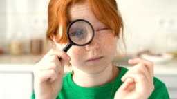 Big eye watching. Funny little girl freckle face looking through magnifier smile