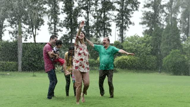 big family enjoying in the rain season, delhi, india - maglietta video stock e b–roll