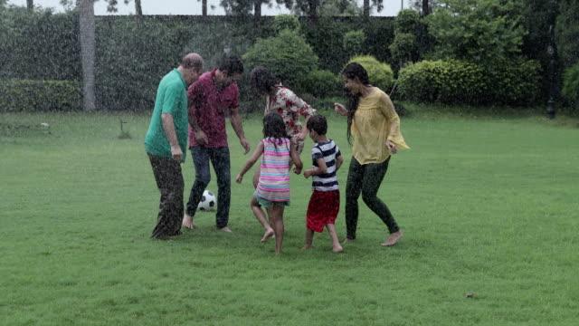 Big family playing soccer in the rain season, Delhi, India