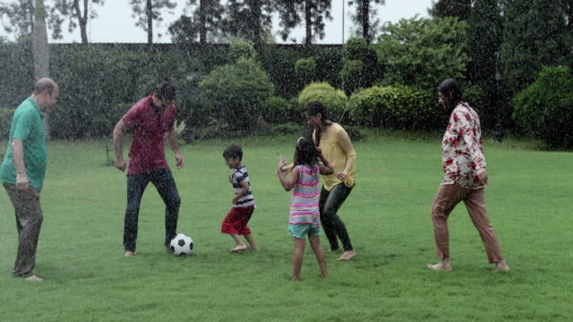 Big family playing soccer in the rain season, Delhi, India