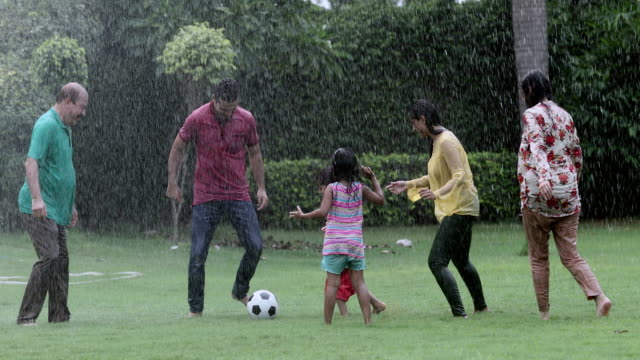 big family playing soccer in the rain season, delhi, india - 50 54 years stock videos & royalty-free footage