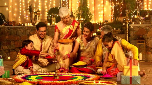 Big family preparing rangoli, Delhi, India