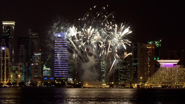 vídeos de stock e filmes b-roll de big fireworks in modern city at night - doha